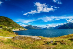 islandiia-gory-zaliv-bereg-domiki-derevia-solntse-nebo-oblak